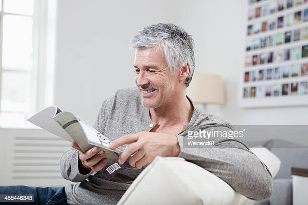 Germany, Bavaria, Munich, Mature man reading magazine on couch, smiling