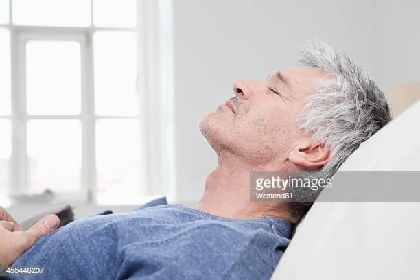 Germany, Bavaria, Munich, Mature man relaxing on sofa