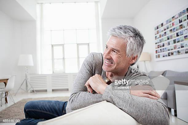 Germany, Bavaria, Munich, Mature man sitting on couch, smiling