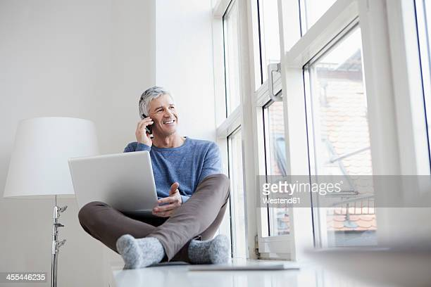 germany, bavaria, munich, mature man talking on mobile and using laptop, smiling - men in white socks fotografías e imágenes de stock
