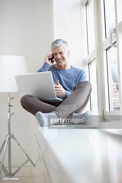 Germany, Bavaria, Munich, Mature man talking on mobile and using laptop, smiling