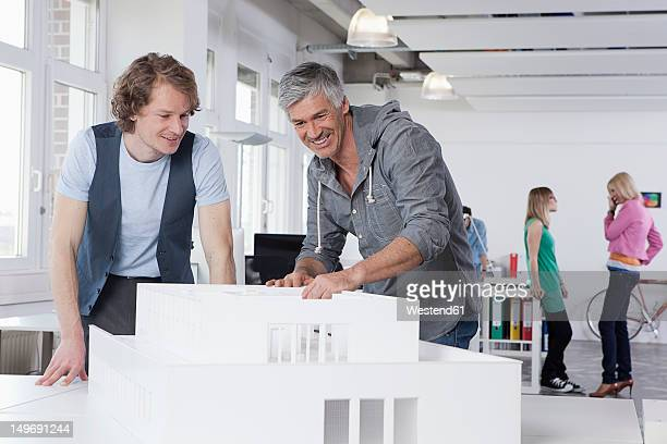 Germany, Bavaria, Munich, Men watching architectural model in office, colleagues talking in background