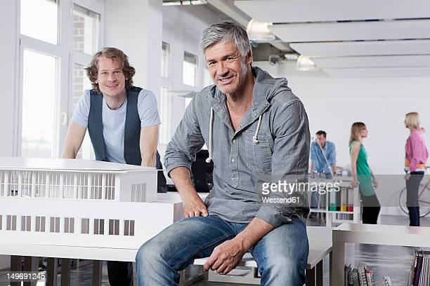 Germany, Bavaria, Munich, Men with architectural model in office, colleagues talking in background