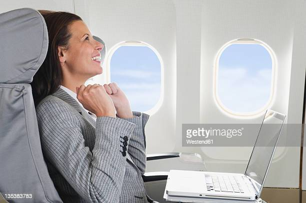 Germany, Bavaria, Munich, Mid adult businesswoman with laptop in business class airplane cabin