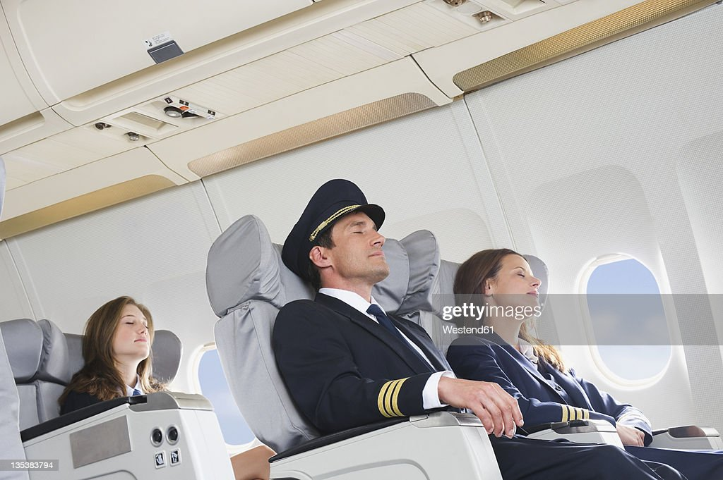 Germany, Bavaria, Munich, Mid adult flight personnels and stewardess resting in business class airplane cabin : Stock Photo