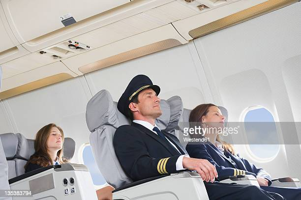 germany, bavaria, munich, mid adult flight personnels and stewardess resting in business class airplane cabin - uniform cap stock pictures, royalty-free photos & images