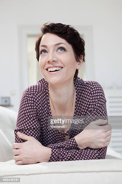 Germany, Bavaria, Munich, Mid adult woman relaxing on couch, smiling