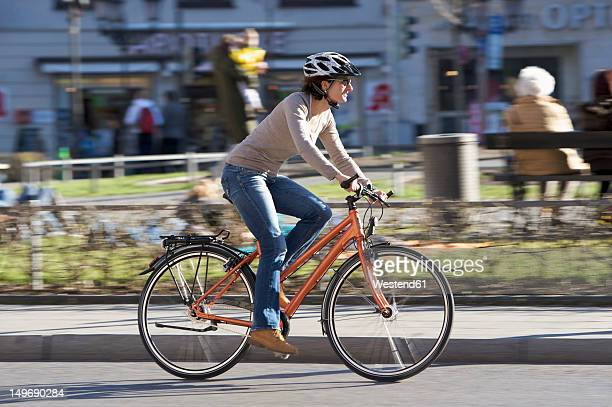germany, bavaria, munich, mid adult woman riding bicycle - cycling helmet stock photos and pictures