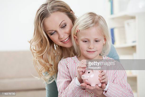 Germany, Bavaria, Munich, Mother and daughter holding piggy bank, smiling