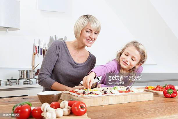 Germany, Bavaria, Munich, Mother and daughter preparing pizza in kitchen
