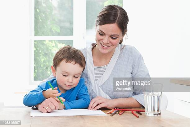 Germany, Bavaria, Munich, Mother and son (2-3 Years) painting picture in kitchen