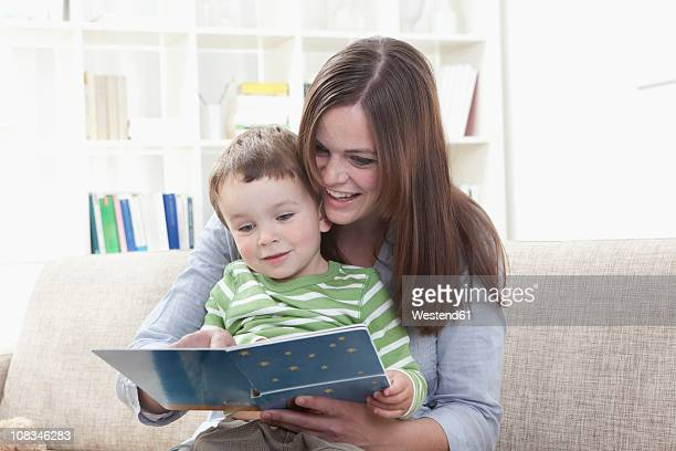 germany, bavaria, munich, mother and son (2-3 years) reading book in living room - 2 3 years stock pictures, royalty-free photos & images