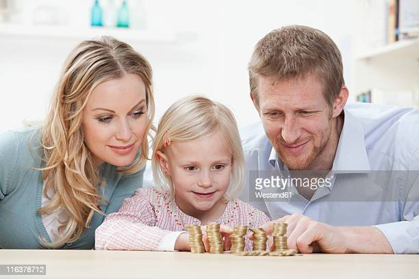 Germany, Bavaria, Munich, Parents and daughter counting coins at table, smiling