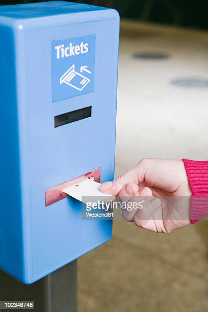 Germany, Bavaria, Munich, Woman inserting ticket in ticket barrier at subway station, close-up