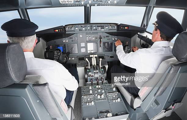 germany, bavaria, munich, pilot and co-pilot piloting aeroplane from airplane cockpit - co pilot stock photos and pictures