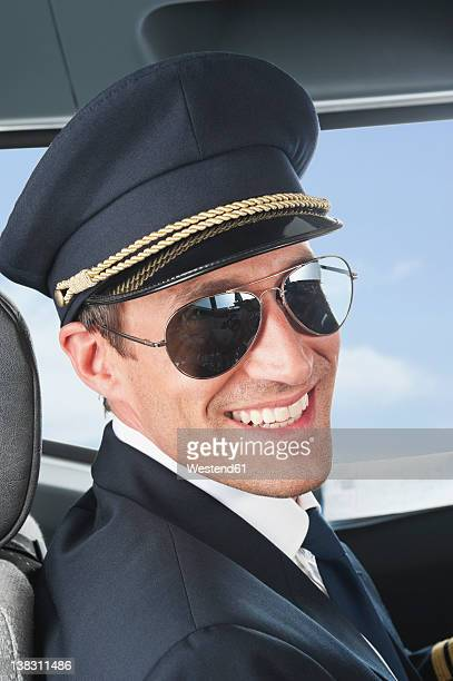 Germany, Bavaria, Munich, Pilot wearing aviator glasses in airplane cockpit, close up
