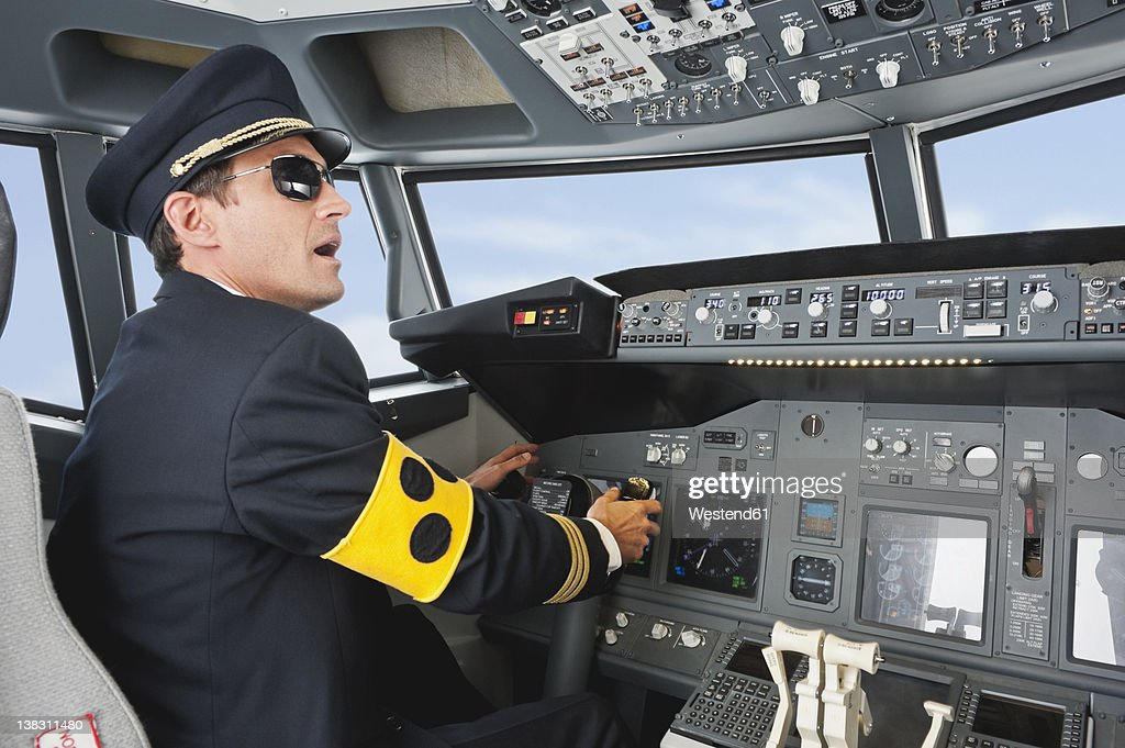 Germany, Bavaria, Munich, Pilot with armlet for blind piloting aeroplane from airplane cockpit : Stock Photo