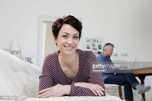Germany, Bavaria, Munich, Portrait of woman leaning on sofa while man using laptop in background
