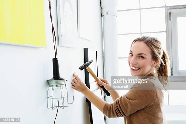 Germany, Bavaria, Munich, Portrait of young woman hammering wall, smiling