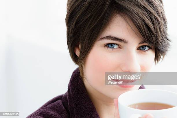 Germany, Bavaria, Munich, Portrait of young woman holding tea cup, close up