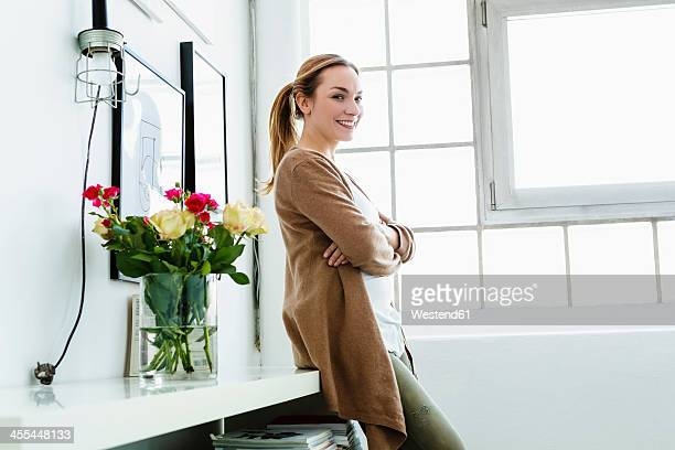 Germany, Bavaria, Munich, Portrait of young woman leaning on shelf, smiling