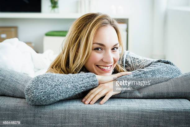 Germany, Bavaria, Munich, Portrait of young woman relaxing on couch, smiling