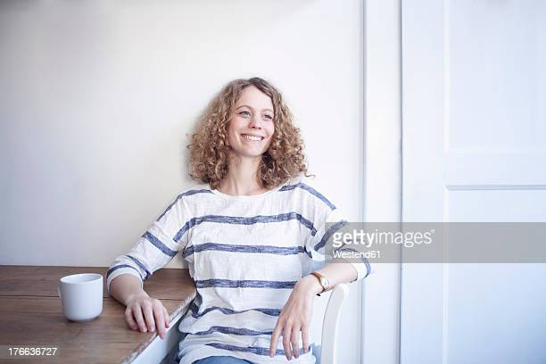Germany, Bavaria, Munich, Portrait of young woman sitting at table, smiling