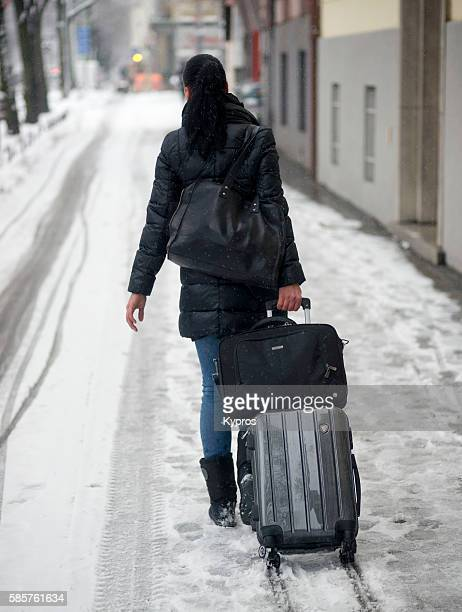 Germany, Bavaria, Munich, Rear View Of Woman Pulling Wheeled Luggage On Snow Covered Street