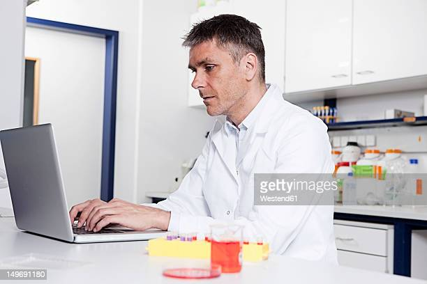 Germany, Bavaria, Munich, Scientist using laptop in laboratory