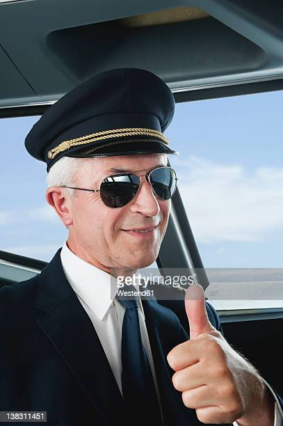 germany, bavaria, munich, senior flight captain wearing aviation glasses with thumbs up in airplane cockpit, smiling, close up - uniform cap stock pictures, royalty-free photos & images