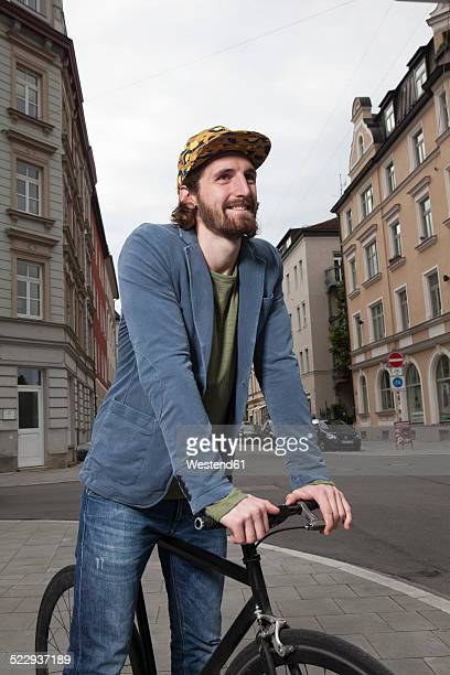 Germany, Bavaria, Munich, smiling young man wearing basecap standing on pavement with his racing cycle