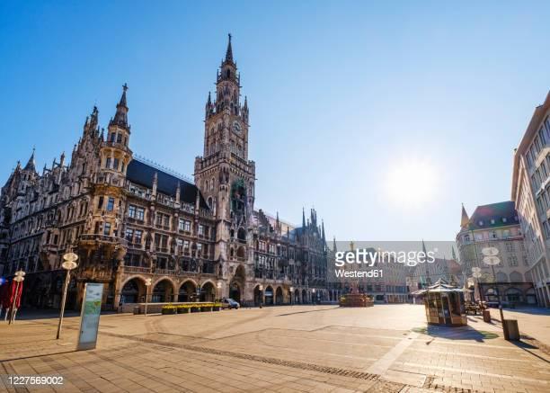 germany, bavaria, munich, sun shining over deserted marienplatz - münchen stock-fotos und bilder
