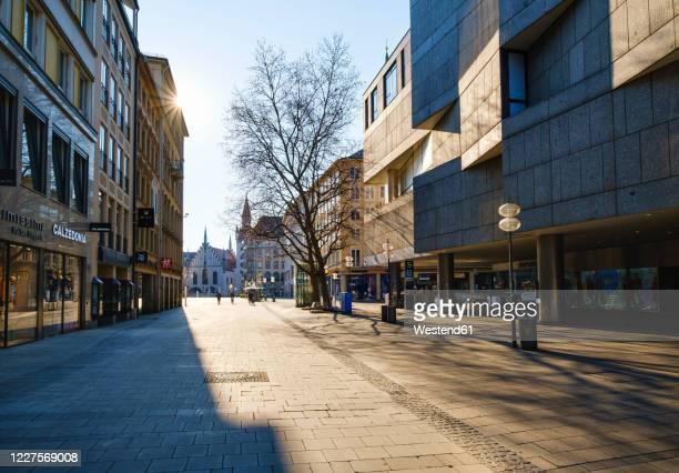 germany, bavaria, munich, sun shining over empty neuhauser strasse street - stadt stock-fotos und bilder