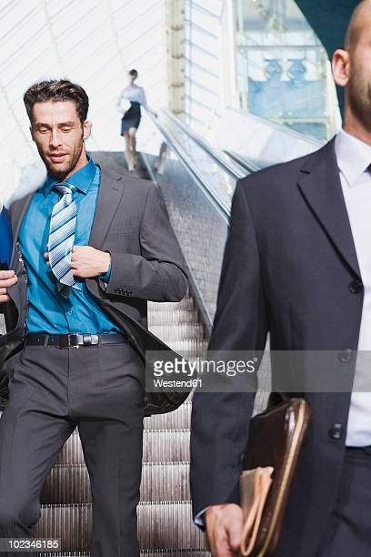 Germany, Bavaria, Munich, Three businesspeople on escalator, one of them running downstairs