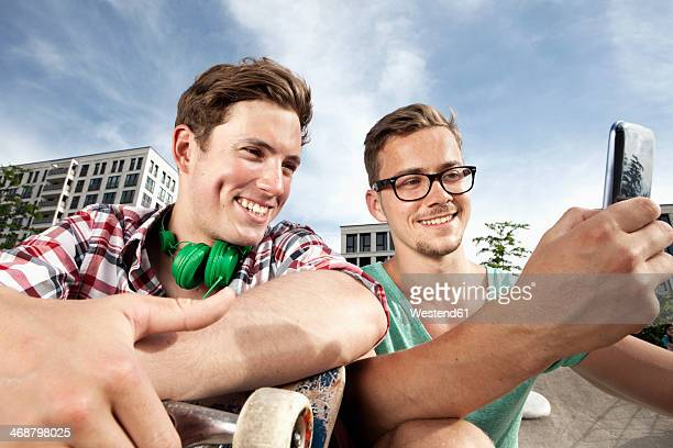 Germany, Bavaria, Munich, Two friends with skateboard and smartphone