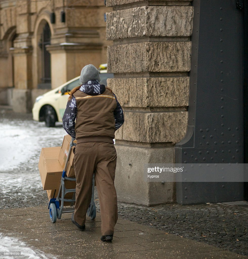 Germany, Bavaria, Munich, View Of Delivery Man Pushing Cart With Boxes : Stock Photo