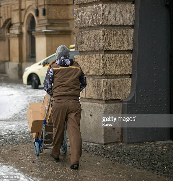 Germany, Bavaria, Munich, View Of Delivery Man Pushing Cart With Boxes