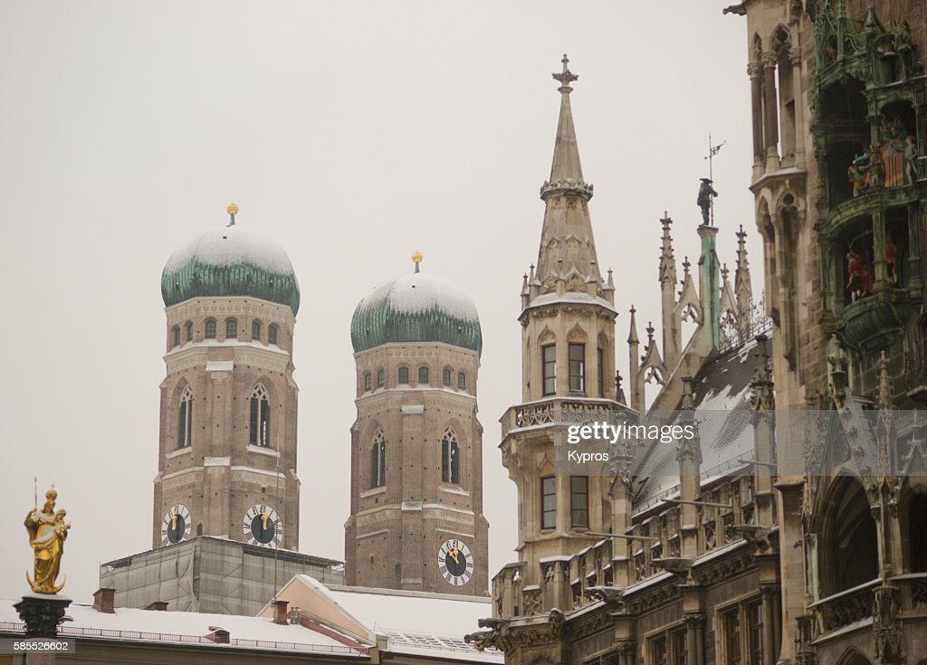 Germany, Bavaria, Munich, View Of Snow Covered Bavarian Church. Church Of Our Lady (German: Dom Zu Unserer Lieben Frau) With Tower Of The New Town Hall, Or Neues Rathaus At Marienplatz. : Stock Photo