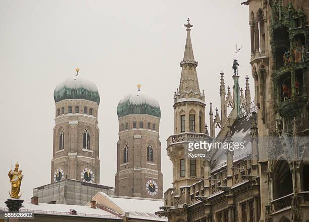 Germany, Bavaria, Munich, View Of Snow Covered Bavarian Church. Church Of Our Lady (German: Dom Zu Unserer Lieben Frau) With Tower Of The New Town Hall, Or Neues Rathaus At Marienplatz.