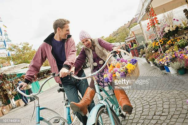 Germany, Bavaria, Munich, Couple messing about on bicycles in Viktualienmarkt