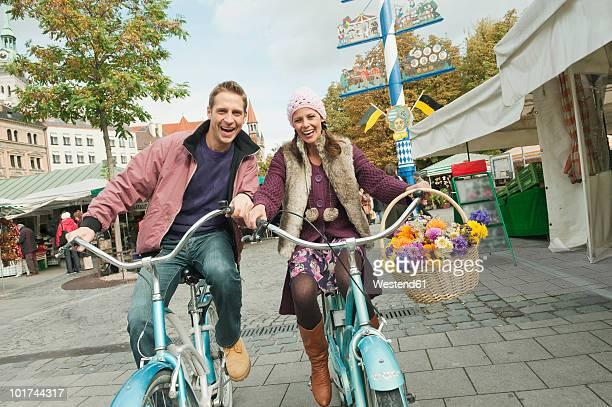 Germany, Bavaria, Munich, Couple cycling in Viktualienmarkt, portrait