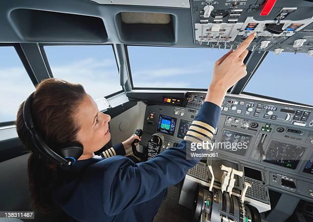 Germany, Bavaria, Munich, Woman flight captain piloting aeroplane from airplane cockpit