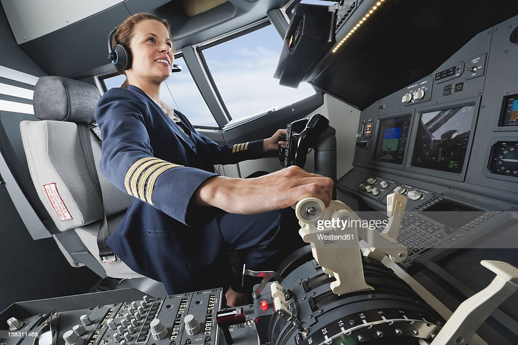 Germany, Bavaria, Munich, Woman flight captain piloting aeroplane from airplane cockpit : Stock Photo