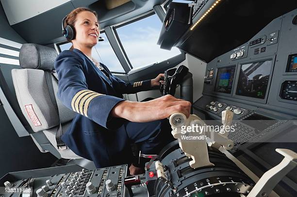Germany, Bavaria, Munich, Woman flight captain piloting aeroplane from airplane cockpit