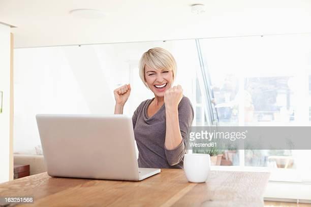 Germany, Bavaria, Munich, Woman happy while using laptop