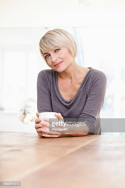 Germany, Bavaria, Munich, Woman holding cup at table