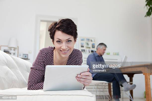 Germany, Bavaria, Munich, Woman holding digital tablet while man using laptop in background