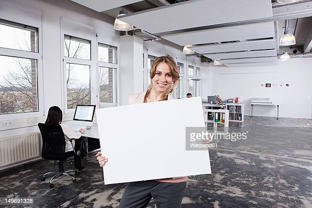 germany, bavaria, munich, woman holding placard, colleagues working in background - halten stock-fotos und bilder