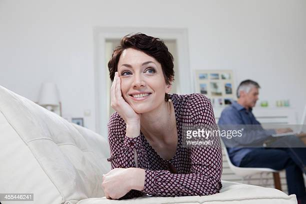 Germany, Bavaria, Munich, Woman leaning on sofa while man using laptop in background