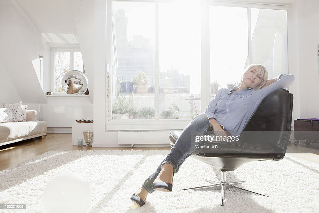 Germany, Bavaria, Munich, Woman relaxing on chair in living room : Stock Photo